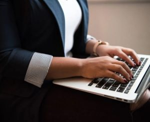 woman in professional attire typing on laptop