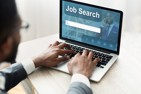 Black man using laptop with job search engine on screen